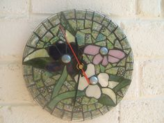 First mosaic clock I made using broken crockery for background and cutting glass shapes for petals and leaves. Glass nuggets for the flower centres.