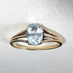 A pretty mid century 10k yellow gold ring set with a beautiful oval aquamarine. The genuine faceted stone has great clarity and color. The modernist