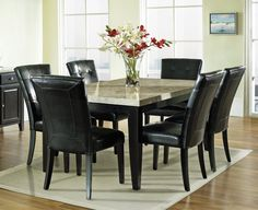 Simple Small Dining Room Idea with Black Leather Upholstered Dining Chairs and Granite Top Table and Colorful Flowers in Glass Vase also Beige Area Rug and Laminate Wood Flooring