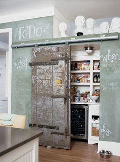 A green chalkboard wall and sliding interior barn door for pantry