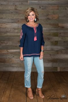 Molly Top is boho charm! This navy, peasant style top has a gathered round neckline trimmed in pink and white embroidery and a button keyhole with tassel tie closure. Featuring 3/4 sleeve with button