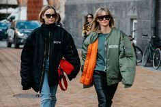 two women on the street in bomber jackets