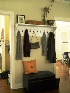 Make an entry wall useful with a shelf with hooks.  Now you have a coat rack. Easily. Inexpensively. Add a bench or a bench ottoman for storage.