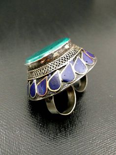 This is a huge Afghan Kuchi Tribal Indian Nepali Ethnic Ring. A beautiful Extra large Afghan Kuchi Tribal Handmade Boho Antique Ring. This is one of the biggest ring in my collection of jewelry. Its a two finger ring. Its a typical Lamp shade cover design ring. The Golden filigree work on this ring is very intricate. A Huge Green Jasper Stone is inlaid on the top of the ring all surrounded by beautiful hand carving and filigree and lapis tear shaped stones. These kind of big rings are worn…