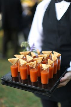 These comforting tomato soup shots with mini grilled cheese sandwiches would be the ultimate passed hors d'oeuvres at a wedding reception.