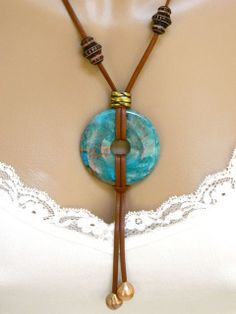 This blue jasper donut necklace is made with brown, deer skin leather, cream colored freshwater pearls, carved wooden beads and an antique brass large hole bead. The long, handmade necklace is quite striking. The wooden beads can be positioned on the leather cord to your liking as they are not clued in place. The end of the necklace is finished with gold plate cord ends and a gold plate lobster claw clasp. The necklace is approximately 20 inches long with a 3.25 inch drop for the leather…