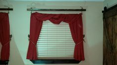 repurposed scarf valance hung on a hollow curtain rod with a rope pulled through it, knotted, then pulled through a stained 2x2.  Rope tie backs finish it off.