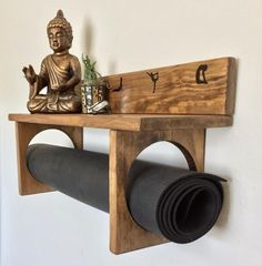 Meditation room. YogaWares makes specialty yoga mat holders for you or your favorite yogi.  Made entirely of real wood, hand stained and decorated with white vinyl. A large full size shelf at the top to place your meditation or decorative items and custom mat holder rings at the bottom. It ships completely assembled. Proper preparation of the wood includes, sanding, pre-staining, staining and sealing. This is essential to the longevity of your board.  Measuring 23.5 x 7 x 9 this is a…