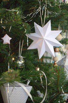 8 zackiger Stern aus weißem Papier am Weihnachtsbaum gehängt