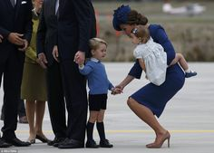 Kate held her son's hand while carrying Princess Charlotte as Prince William spoke with officials after arriving in Victoria