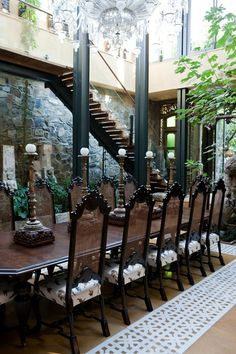 I can't tell whats going on in this picture- but I kinda like it. Old world table & chairs, modern glass staircase, industrial beams, stone walls, a crazy inlay, and a tree?