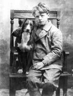 Boy and his dog posing on a chair, vintage photo.