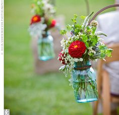 Vintage Mason jars filled with red, green, and white flowers were hooked to guests' wooden chairs, marking either side of the aisle.