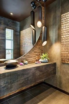 Textured wall (stacked stone veneer) with a ginormous round mirror and a metallic vessel sink [vacation retreat designed by Len Cotsovolos and LC²Design ]
