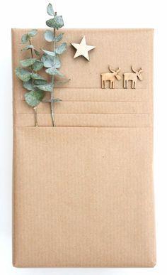 Geschenkverpackung aus Packpapier. Durch mehrere Lagen Papier und kleinen Figuren entsteht der Effekt einer Landschaft.
