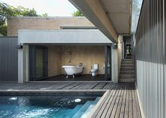 Brick and concrete house in Chiang Mai, Thailand, by SO with a glazed bathroom overlooking the swimming pool.