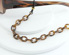 Retro Vintage Tortoise Shell Eyeglass Chain for Women.  Vintage Chic acrylic Tortoise Shell Link Chain is a great accessory for sunglasses and reading glasses.  Total length is 26 inches.  ~~Fitted with premium quality black eyeglass holders that are custom fitted with Gold Rondelle beads for a Chic and secure fit on all sizes of eyeglass arms.