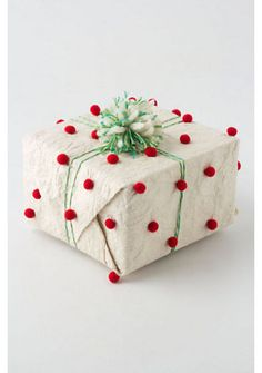 This wrapping paper by Anthropologie is way too expensive.  It would be easy and inexpensive to glue or hot glue little red pom poms to wrapping paper.