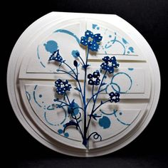 """By Eileen Godwin. Dies: Memory Box """"Bella Bouquet""""; 4 largest Spellbinders circles. White linen CS. Fold piece of CS in half; lay largest circle die so it hangs over fold. Cut  emboss. Cut  emboss other circles. Layer 2nd largest circle on card. Stamp design on smallest circle; cut in half. Cut 1 piece in half again; cut other piece into 3 parts as shown. Do same cuts for next smallest circle. Layer stamped pieces onto plain pieces. Pop up on card. Die cut flower from blue; pop up on card."""
