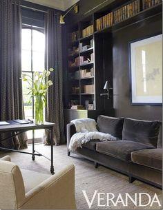 A gray velvet sofa is surrounded by dark built-in bookshelves.