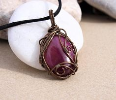 Beautiful purple tigers eye wire wrapped pendant. For the wrapping I used enameled copper wire in gunmetal colors. The wire wrapped pendant is 38x28mm and it comes on black leather or black faux suede cord 18 inches. I will ship your pendant in a paper box wrapped with a beautiful ribbon, ready for gift giving!  The order is shipped in 1-2 business days after purchasing. After shipment you will have a tracking number in your e-mail inbox. The estimated delivery for Europe is 4-10 business…