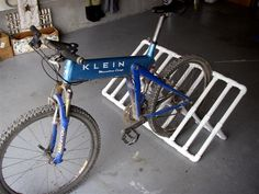 PVC Pipe Bike Rack.  This is awesome!  Can put in the garage & in the back of truck. Bike Floor Stand, Bicycle Stand, Farm Projects, Pvc Projects, Wooden Projects, Home Projects, Pvc Bike Racks, Garage Organization, Garage Storage