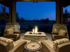 Outdoor Fireplaces and Fire Pits That Light Up the Night: This covered outdoor oasis is party-ready with plenty of seating and a stunning fire feature right in the middle. The stone-surround gas fire pit is instantly the focal point of the entire space and invites guests to gather around the campfire during the summer or winter months. From DIYnetwork.com