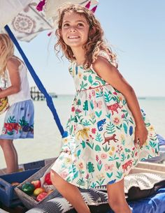 This smock-style dress is a dreamy outfit for running around the park. It's fully lined, but we've kept it breezy in cotton poplin fabric. Short fluttery sleeves and a detailed trim add delicate touches to this knee-length design. Buttons down the back make getting dressed for that picnic party super-easy.