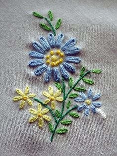 A simple embroidery piece with lazy daisy stitches, French knot center and stem stitch.