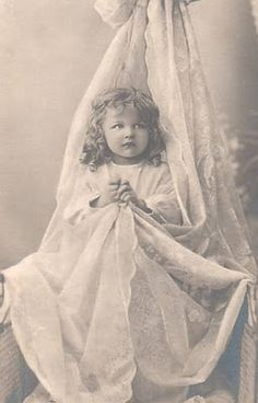 little girl in lace curtain black and white photo
