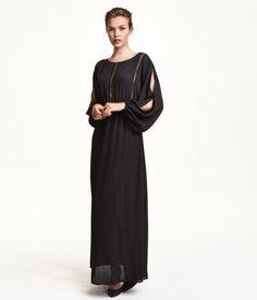 En lång klänning i vävd kvalitet med hålbroderier fram och bak. Klänningen har lång, vid ärm som är öppen upptill och har resår vid ärmslut. Avskuren med resår i midjan. Utställd kjol. Ofodrad.