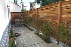 Modern Wood Fence Design With Green Plants Around Fence. Contemporary home fencing and gates for modern wood fance design. Tricks for Using Modern Wood Fence Designs.