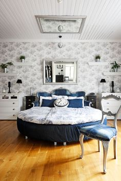 Ikean pyöreä sänky on saanut päädykseen vanhan sohvan, joka on päällystetty vanhoilla Levi's-farkuilla. Sängyn molemmin puolin sijoitetut senkit on ostettu Kodin Tyylistä ja hyllyt Ellokselta. Kellotyyny on hankittu H&M Homesta, peilit Ikeasta ja tummat yöpöydät Indiskasta.