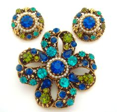 "Signed Florenza ornate curvy ribbon bow pin and earring set. Gorgeous shades of blue and green rhinestones set in Florenza's typical fancy Victorian designed gold tone metal. This lovely dimensional pin measures 2"" in diameter and the clip on earrings measure 1"" in diameter. $115.00. Free shipping in the US. Questions? PM me via FB. PayPal Only."