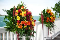 Rich reds, rusts and orange pedestal arrangements by Love In Bloom Florist at Ocean Key Resort, Key West. Photo Transier Photography