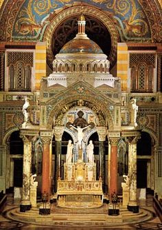 Altar St. Louis Cathedral - Inside, the aroma of ancient brick masonry greets the visitor. One thinks at once of an old French monastery, although stone is nowhere. The darkened entry gives way to a bright interior with painted surfaces everywhere. The eye is drawn to the great high Rococo altar, where gilded and fluted columns of the Corinthian order support a busy entablature. Two rows of wooden columns divide the church into nave and side aisles, with a mute upper gallery where