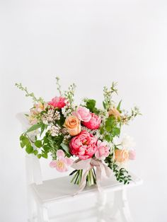This bouquet was inspired by spring and includes apple blossoms and peonies with fresh foliage and tulips in keeping with very seasonal and fragrant blooms. The arrangement features a bright colour palette and is lush and romantic yet whimsical and rich in texture.