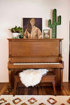 Living room with a vintage piano with vintage art and a neon cactus sign propped above, and a lamb throw