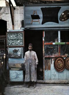 A painter stands in the doorway of his shop Autochromes taken by Gervais Courtellemont and W. Robert Moore for National Geographic.