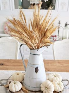 Use an antique pitcher as a vase to hold faux wheat. Add neutral-colored pumpkins at the base of the pitcher to complete the look. Get the tutorial at Shabby Fur Blog.