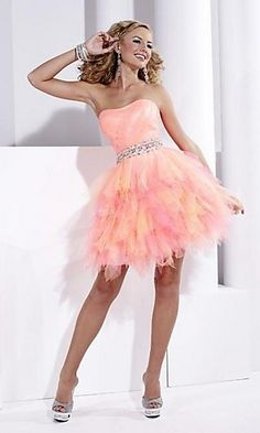 Go for fun and flirty with a feminine touch for prom in this short Hannah S party dress. This short cocktail dress features a semi-sweetheart neckline on a fitted bodice accented with directional pleating. A sparkling waistband with beaded crystal filigree accents the waist. Shimmering tiers of ombre chiffon in a hankerchief design set this stunning short formal dress apart from the crowd for a fun and flirty look for prom or your next special occasion party.