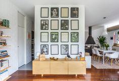 Parede com composição de quadros e rack de madeira separa a área comum dos quartos.