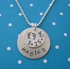 custom hand stamped silver baby name and birthdate necklace with footprints. $38.00, via Etsy.
