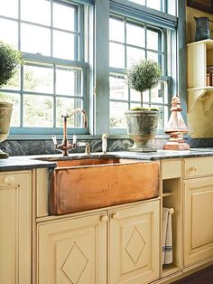 copper farmhouse sink mixes beautifully with the blue window frames - via BHG Farmhouse Sink Patina
