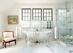 A Hugo Köcke painting hangs in the master bath of a Baton Rouge, Louisiana, home by architect Bobby McAlpine and designer Ray Booth; the tub and the bath and shower fittings are by Lefroy Brooks.