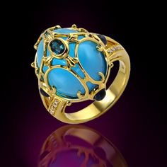 R5254BT  18K yellow gold half round ring features one natural alexandrite in a bezel setting atop a 19.00 ct. cabuchon blue topaz accented by four round shape blue sapphires with a 0.70 ct. tw and an ensemble of natural white diamonds. Also available in white gold.