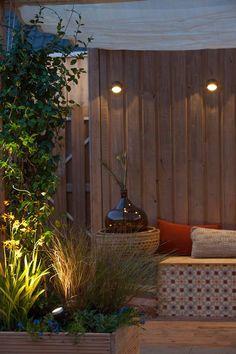 In deze tuin is wandlamp BLINK DARK bevestigd aan de schutting. Zo creeër je een sfeervolle plek in de tuin met buitenverlichting. #tuin #schutting #wandlamp #tuinverlichting