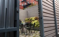 Enclosed by tall fencing and overlooked by neighboring buildings, this small space could have been neglected. Instead, it has been turned into a congenial space in which to escape outside for an evening meal or a quiet drink.The small courtyard is surrounded by whitewashed fir walls and paved with setts separated by joints filled with native moss. The colorful planting enlivens the whole scheme.