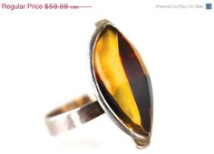 Vintage sterling silver ring set with Baltic amber. It is adjustable, but right now it is a size 7 1/2. Face measures 1 x 1/2. Marked 925. $41.99