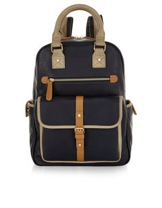 Cool for school - and work, and weekends - this striking top handle backpack is crafted with contrasting trims for a smart, preppy feel. It features a taupe carry handle with coordinating trims on the padded shoulder straps, a spacious front pocket with tab and popper fastening and metal stud and buckle detail, and a zipped compartment with a chunky zip pull tab. At the sides, slip pockets with tab closure provides handy extra storage, and you'll find another pocket in the interior wall.